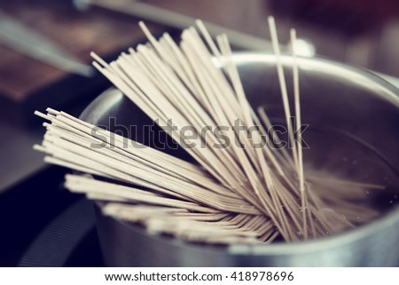 Buckwheat noodles being cooked on induction stove, toned image - stock photo