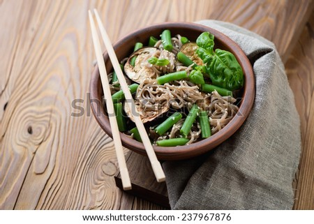 Buckwheat soba noodles with roasted aubergine and beans - stock photo