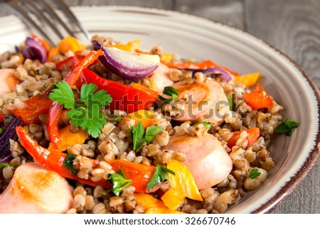Buckwheat with sausages and vegetables on plate and rustic wooden background