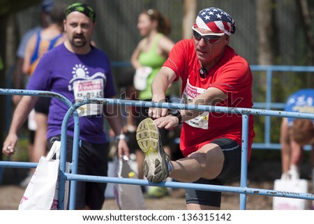 BUDAPEST, HUNGARY - APRIL 21: unidentified marathon runner stretches to cool-down at 28th Telekom Vivicitt�¡ Pro City Run on April 21, 2013 in Budapest, Hungary