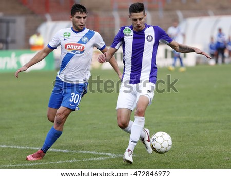 BUDAPEST, HUNGARY - AUGUST 21, 2016: Benjamin Balazs (R) of Ujpest FC competes for the ball with Balint Borbely #30 of MTK during the OTP Bank Liga match between Ujpest FC and MTK at Illovszky Stadium