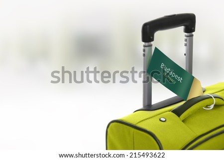 Budapest, Hungary. Green suitcase with label at airport. - stock photo