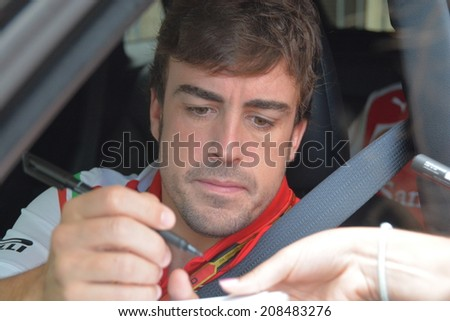 BUDAPEST, HUNGARY-  JULY 27: F1 driver Fernando Alonso stopped by car to give autographs on July 27, 2014 in Budapest. - stock photo