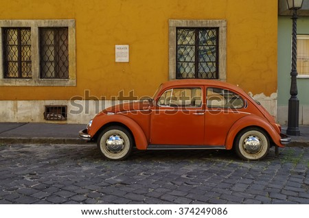 Budapest, Hungary - July 9, 2015: Orange retro economy car - Volkswagen Beetle parked on the old street of Budapest. Side view - stock photo