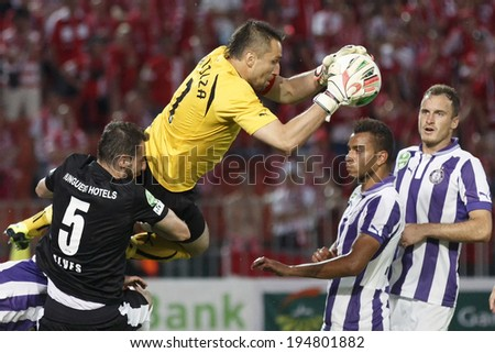 BUDAPEST, HUNGARY - MAY 25, 2014: Szabolcs Balajcza of Ujpest (m) saves beside Pierre-Yves Ngawa and Robert Litauszki (r) during Ujpest vs. Diosgyori VTK Hungarian Cup final match at Puskas Stadium.