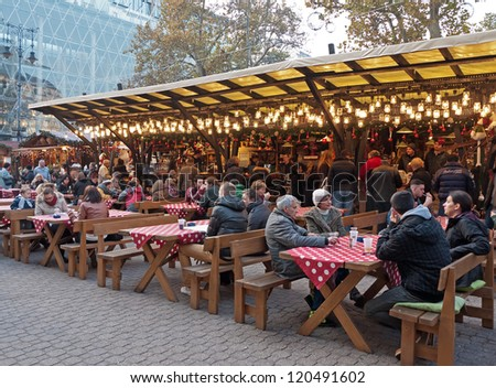 BUDAPEST, HUNGARY - NOVEMBER 20: Tourists enjoy the Christmas market in the city center on November 20, 2012 in Budapest, Hungary. This traditional Christmas fair attracts 600,000 visitors each year. - stock photo