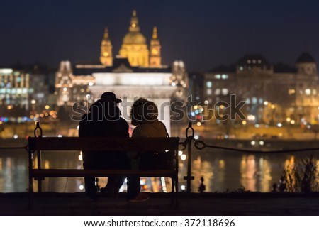 Budapest in night with couple sitting on bench in foreground and St. Stephen Church in background, Europe. - stock photo