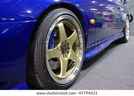 BUDAPEST - MARCH 19: Light-alloy wheel of a blue Nissan Skyline tuned car on international tuning show with reflector lights in Hungexpo on March 19, 2010 in Budapest, Hungary - stock photo