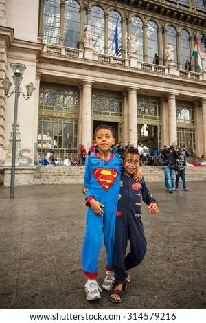 BUDAPEST - SEPTEMBER 4: War refugees children dressed superman at the Keleti Railway Station on 4 September 2015 in Budapest, Hungary. Refugees are arriving constantly to Hungary on  way to Germany. - stock photo
