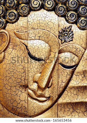 Buddha face carving 3 pieces of wood and gold gilded handcrafts  - stock photo