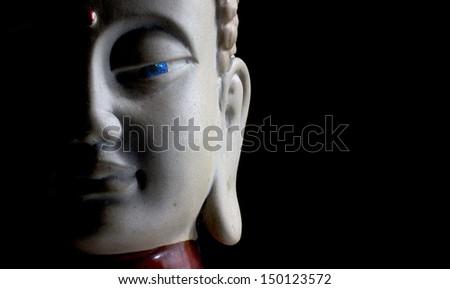 Buddha face with stone eye e black background - stock photo