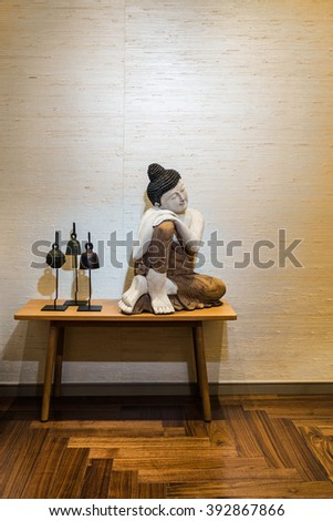 Buddha figurine on a side table with decorative parquet floor - stock photo