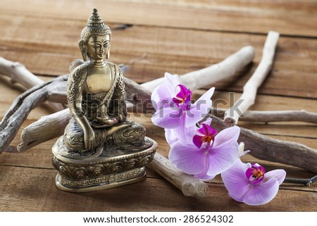 Buddha for spirituality at beauty spa with flower massage and ritual accessories - stock photo