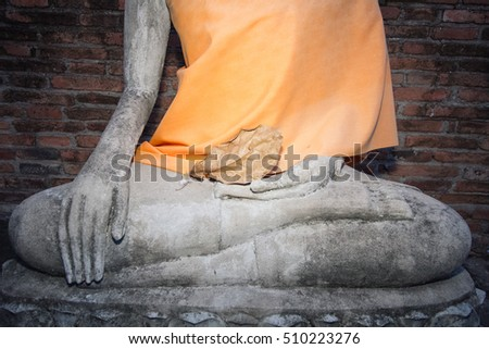 Buddha hand with dried leave in hand with yellow robe