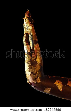 Buddha hand with gold leaf isolated on black background