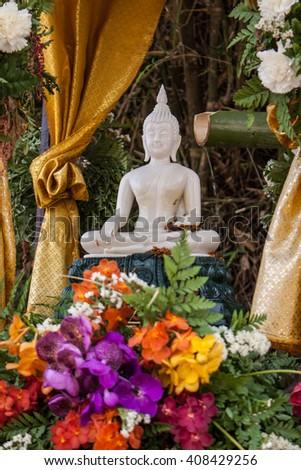 Buddha image and flowers - stock photo