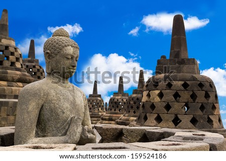 Buddha in Borobudur Temple against blue sky with clouds. Yogyakarta, Central Java, Indonesia. - stock photo