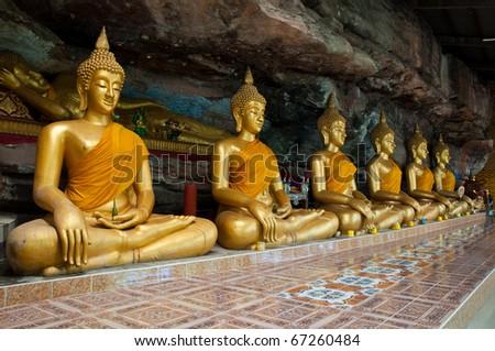 Buddha on stone babkground in cave of Thailand - stock photo