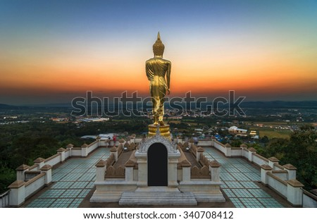 Buddha standing on a mountain at twilight time at Wat Phra That Khao Noi, Nan Province, Thailand, public domain - stock photo
