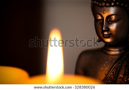 Buddha statue and candle light. - stock photo
