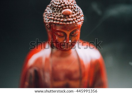 Buddha statue decorated with offerings and flowers. Murti Buddha in the smoke from the incense and floral decorations. Buddhism and its deities, Gautama Buddha - stock photo