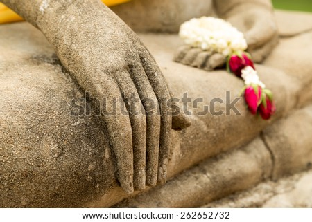 Buddha statue hand and garland (focused on the hand) - stock photo