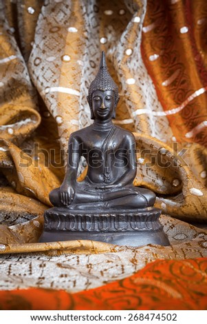Buddha statue in bronze on a silk scarf - stock photo