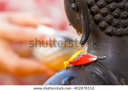 Buddha statue wet water drop with flower close up shot on songkran festival people hand take pouring bowl in blur, Thailand