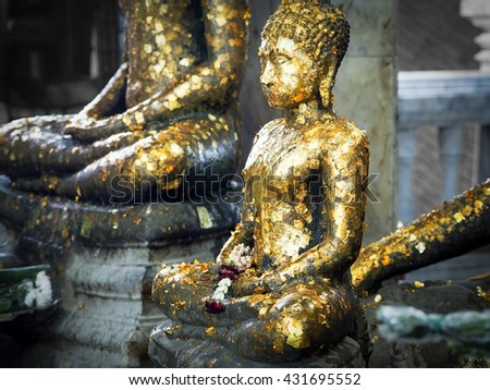 Buddha statue with golden leaf. - stock photo