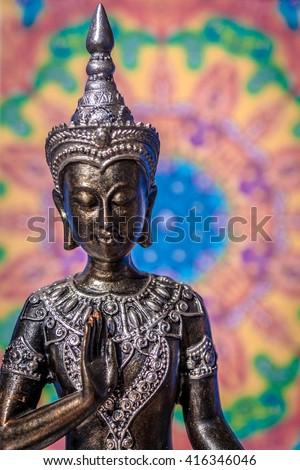 Buddha statue with soft colored mandala background - stock photo