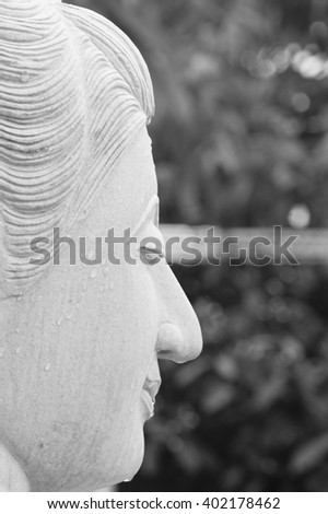Buddha stucco face with water drop on morning time in temple southern thailand with blurry background:Close up,select focus with shallow depth of field:White and Black tone. - stock photo