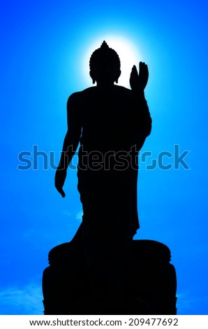 Buddha with sky and sun in the background.