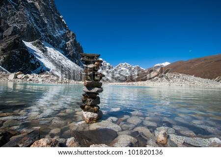 Buddhism: Harmony and balance Stones and Sacred Lake near Gokyo. Religious life in Nepal - stock photo
