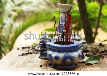 Buddhist altar with joss sticks in a tropical village - stock photo