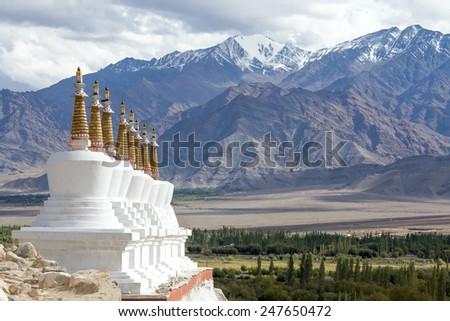 Buddhist chortens (stupa) and Himalayas mountains in the background near Shey Palace in Ladakh, India  - stock photo