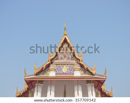 Buddhist church gable under blue sky - stock photo
