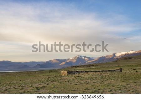 Buddhist landmark among barren terrain with lake and mountain range background - stock photo