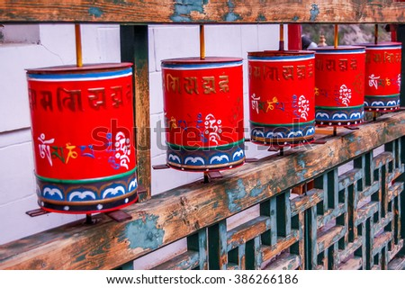 Buddhist mantra Om Mani Padme Hum written in Tibetan script adorns outside of prayer wheels at Mongolian meditation center. To gain merit Buddhists spin prayer wheels clockwise to follow the sun. - stock photo