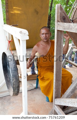 Buddhist monk, hitting the drum in the temple