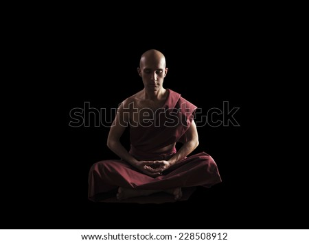 buddhist monk in meditation pose over black background - stock photo