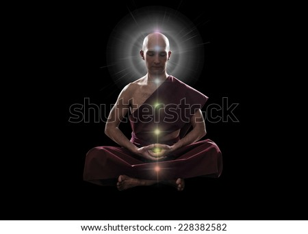 buddhist monk in meditation  pose with colorful Chakras over black background - stock photo