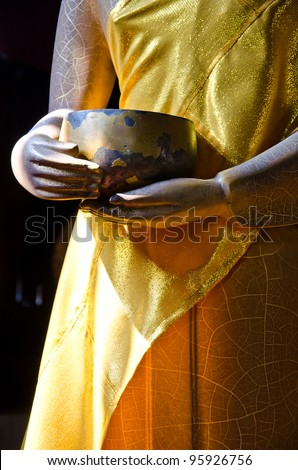 Buddhist monk's alms bowl for donation with gold buddha hand - stock photo