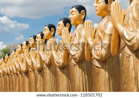 Buddhist monk statues in a row close up in a Buddhist Temple in Sri Lanka - stock photo
