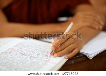Buddhist monk studying Pali, close-up hand and textbook - stock photo