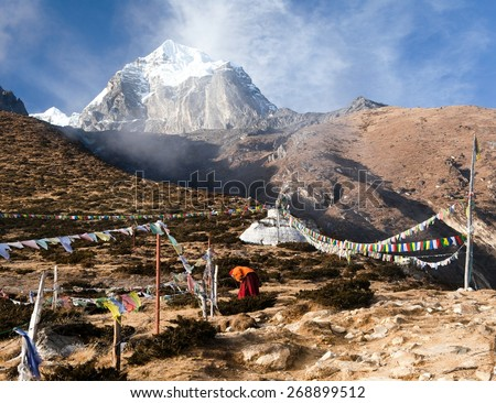Buddhist monk, stupa and prayer flags near Pangboche monastery and Tabuche peak, life in Khumbu valley on the way to Everest base camp, nepal - stock photo