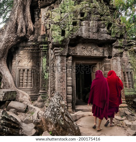 Buddhist monks at Angkor Wat. Ancient Khmer architecture, Ta Prohm temple ruins hidden in jungles. Popular travel destination at Siem Reap, Cambodia - stock photo