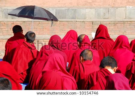 Buddhist monks praying at swayambhunath temple in Kathmandu, Nepal - stock photo