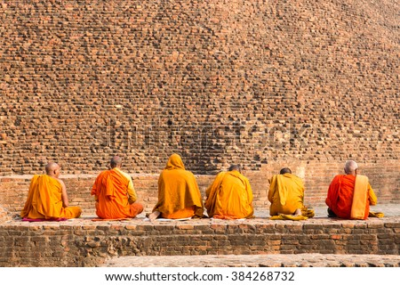 Buddhist monks sitting in front of the old stupa, Kushiingar city, India. - stock photo