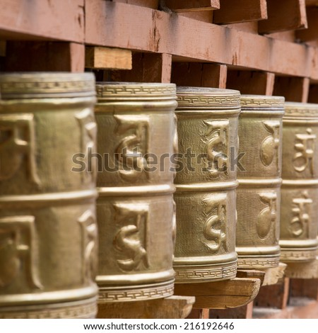 Buddhist prayer wheels in Tibetan monastery with written mantra. India, Himalaya, Ladakh  - stock photo