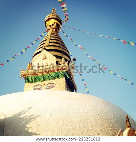 Buddhist shrine Swayambhunath Stupa - vintage filter. Stupa with Buddha wisdom eyes and praying flags - retro effect. Colorful praying flags and stupa, Kathmandu, Nepal. - stock photo